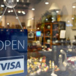store with a Open Visa sign hanging on the door