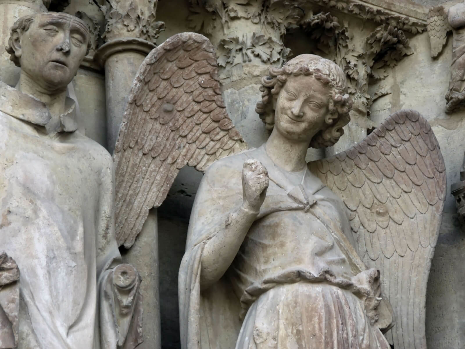 smiling angel on the Reims Cathedral; day trip to reims from paris