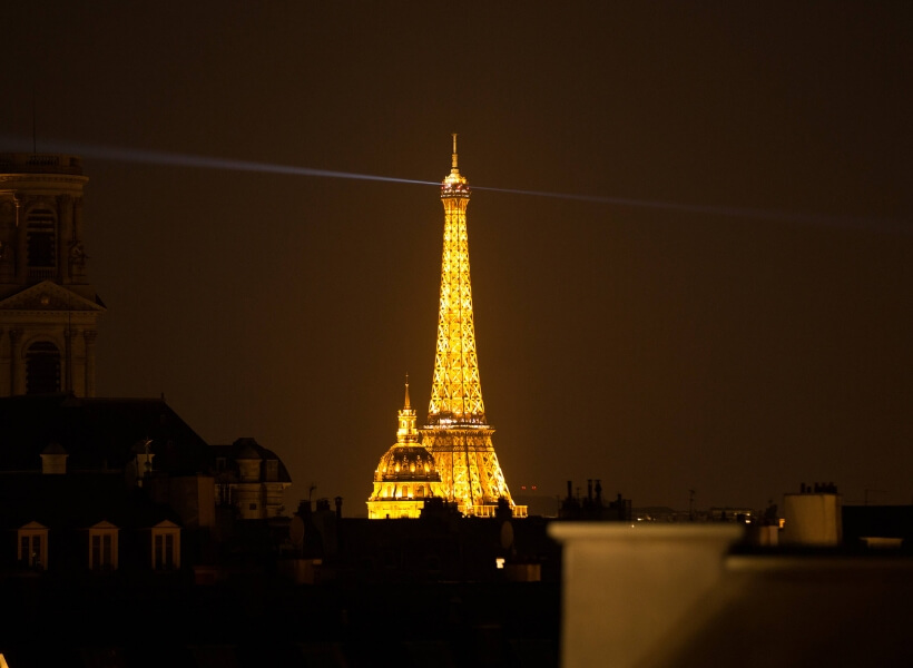 Eiffel Tower seen at night from a Paris rooftop