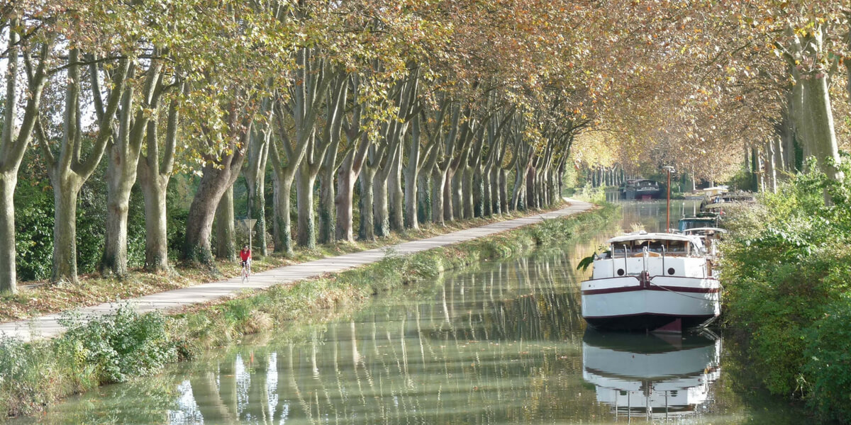 Canal du Midi: bucolic scenery of a canal lined with trees and a barge parked on the side