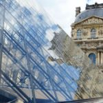 louvre pyramid with reflections of the stone building against the glass