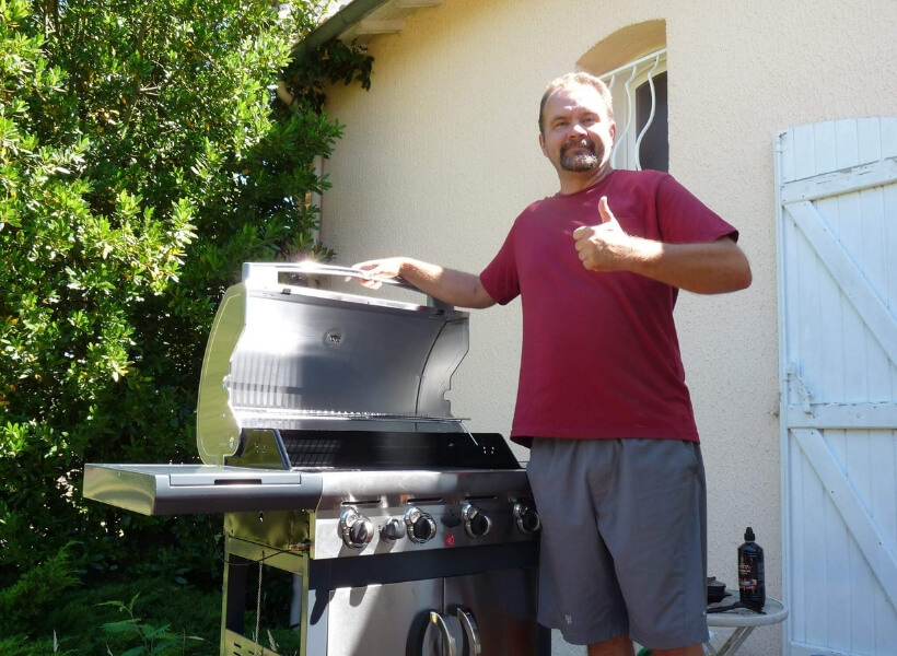 Todd Newman standing near his barbecue and doing the thumbs up sign