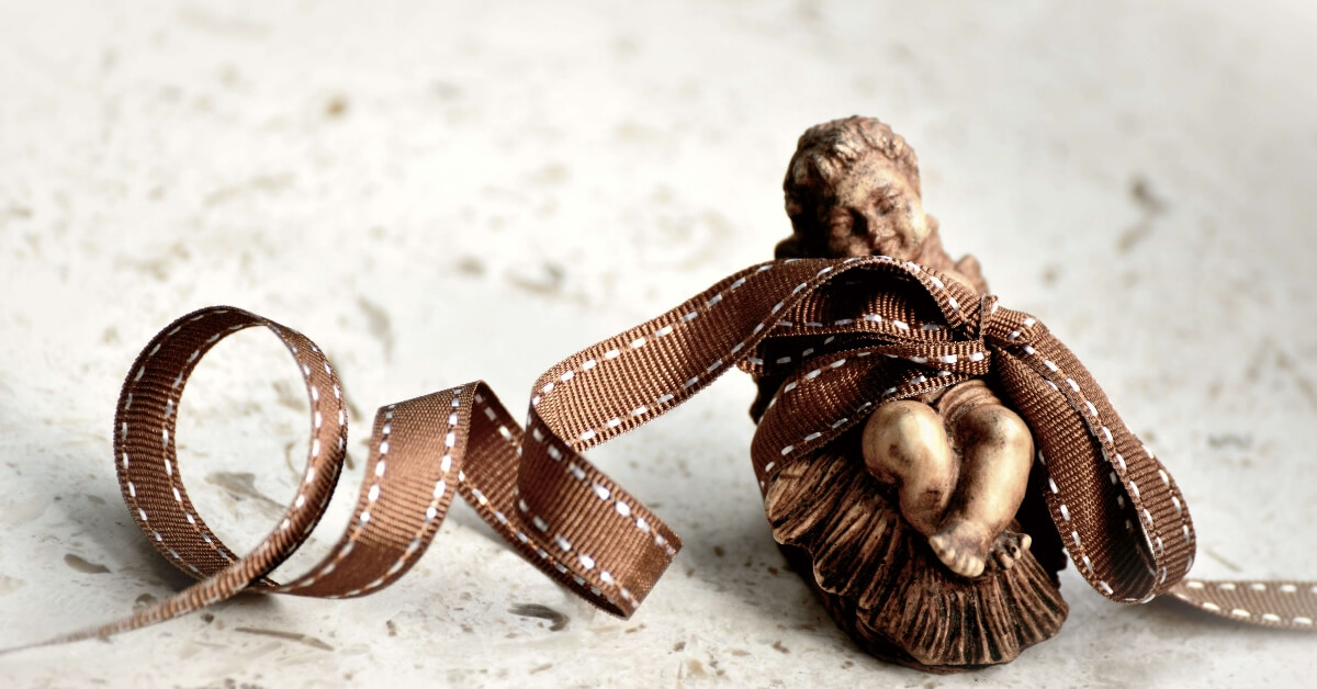Chrismas decoration of the baby Jesus with a brown ribbon wrapped around it
