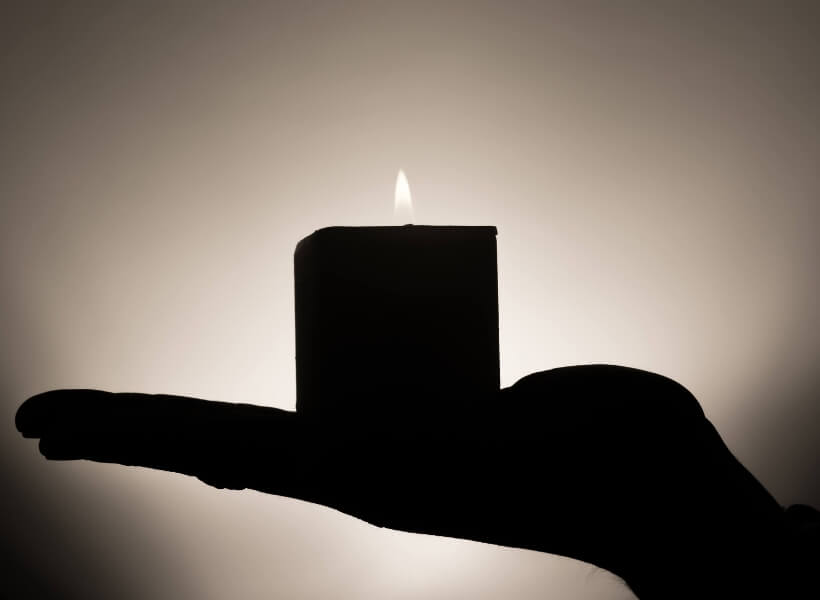 open hand with lit candle on top of it: stay safe in france episode