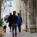 A womand and her guide dog walking through the streets of La Turbie in Provence
