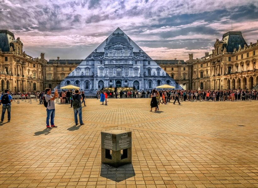 stylised photo of the louvre where the pyramid is see-trough and you can see the building behind it
