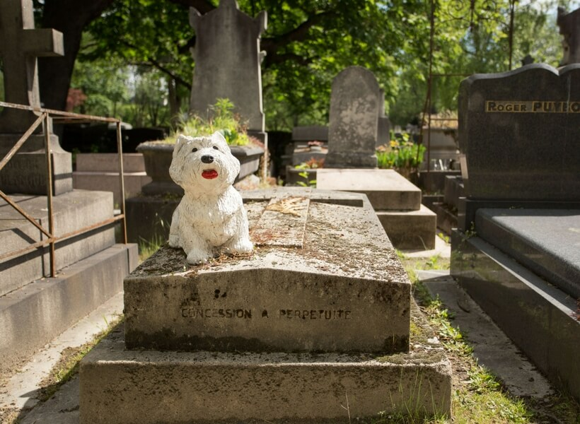 grave with a scotty dog statue on it at pere lachaise cemetery