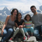 Matt, his wife and daughters in front of snowy mountains in the Alps. Provence and Chamonix episode.