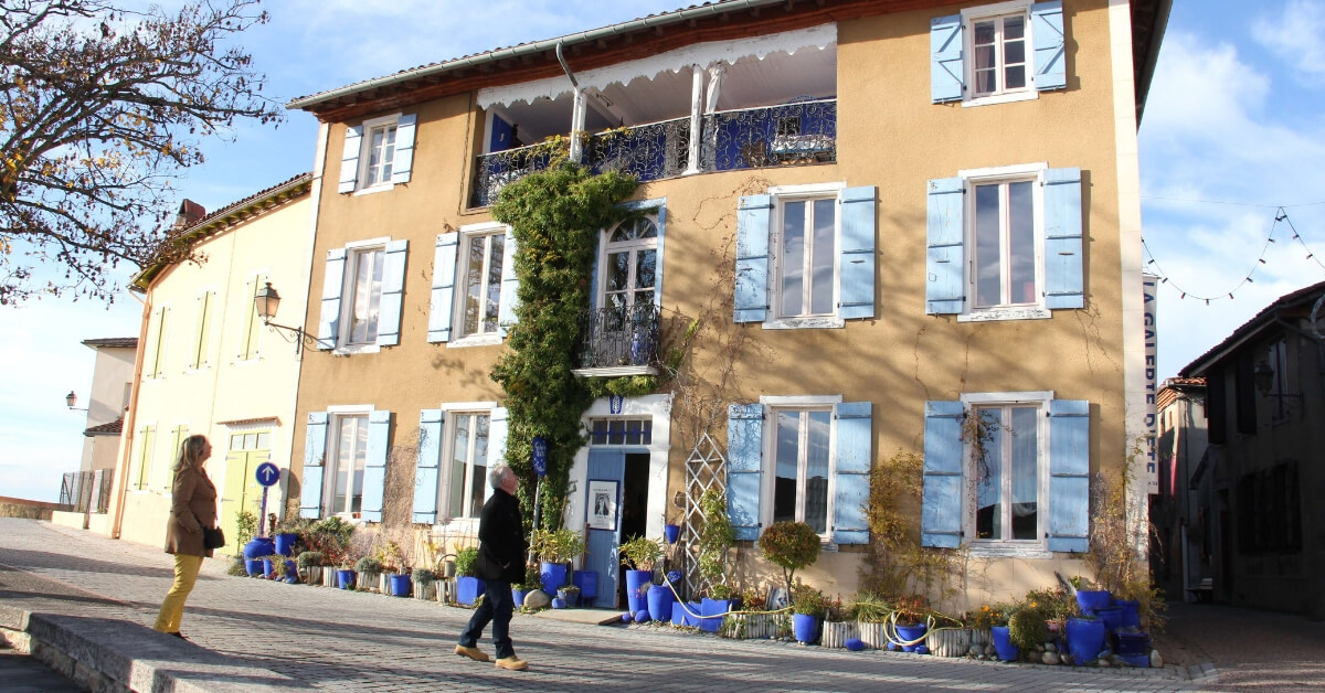 Man and woman visiting the town of Carla-Bayle and walking by a beautiful home with blue shutters and blue planters