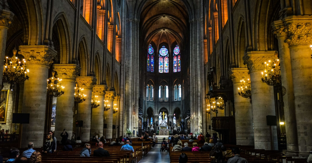 The inside of Notre Dame Cathedral with a wheelchair user in the center isle