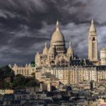 A view of Montmartre and the Sacré Coeur Basilica under a stormy sky