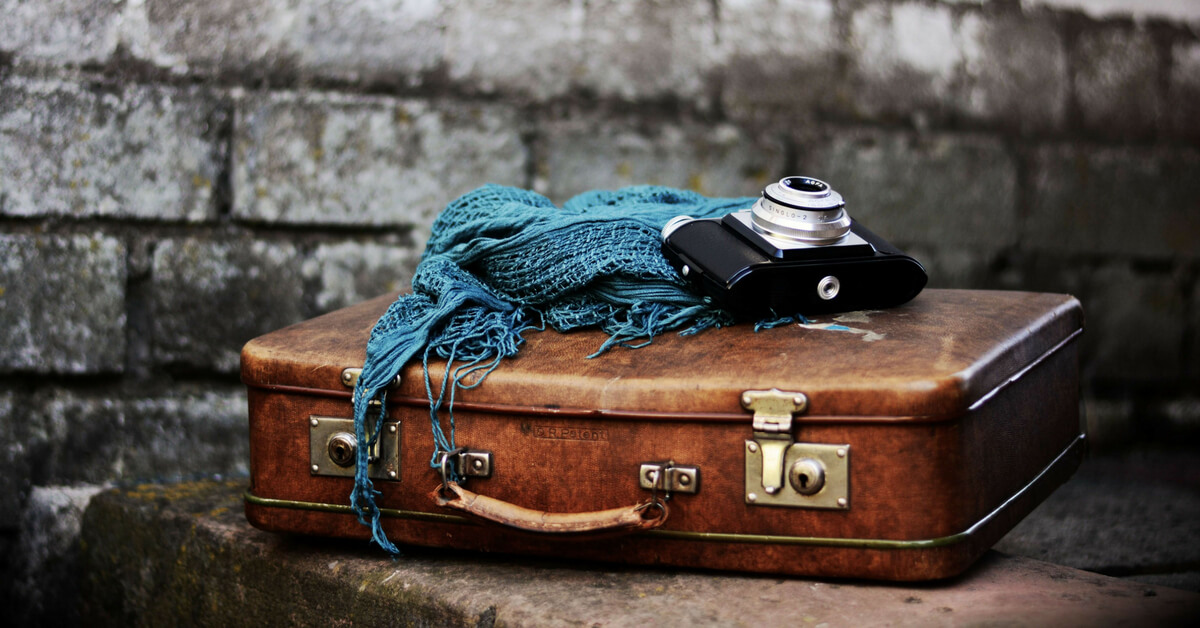 vintage suitcase with blue scarf and old camera on top