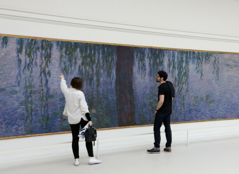 Visitors looking at the Water Lilies at the Orangerie Museum in Paris