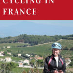 Ilona in her bicycle gear posing in front of a gorgeous French village