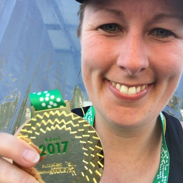 Calee holding her finisher's medal at the Paris Marathon