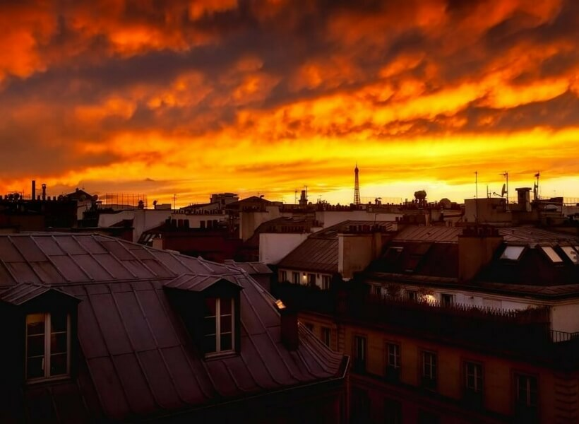 paris rooftops with red and yellow sky; secrets to finding an apartment in paris