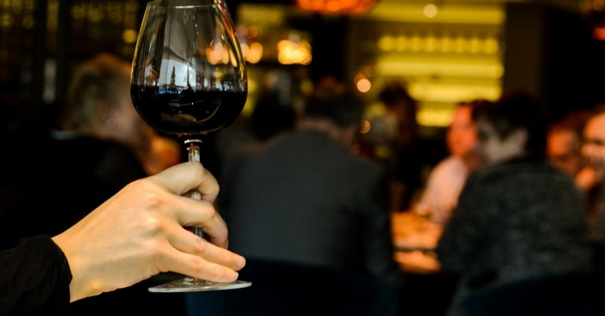 person holding a glass of red wine to smell it during a wine tasting