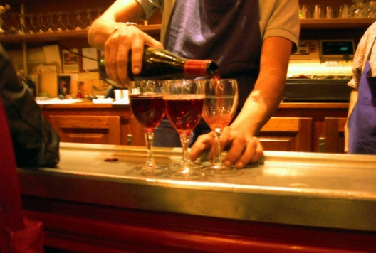 waiter serving 3 glasses of red wine at a bar