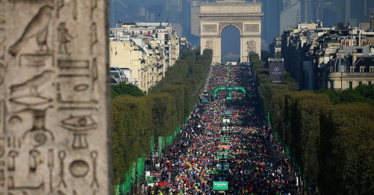 crowd of runners at the paris marathon between the arc de triomphe and place de la concorde