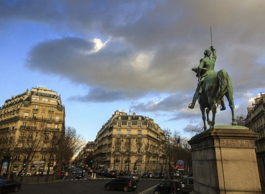 beautiful plaza in paris, statue of man on a horse, hausmanian buildings and dramatic sky