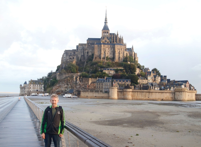 Phil Roberson standing in front of the Mont Saint Michel: Mont Saint Michel History Episode
