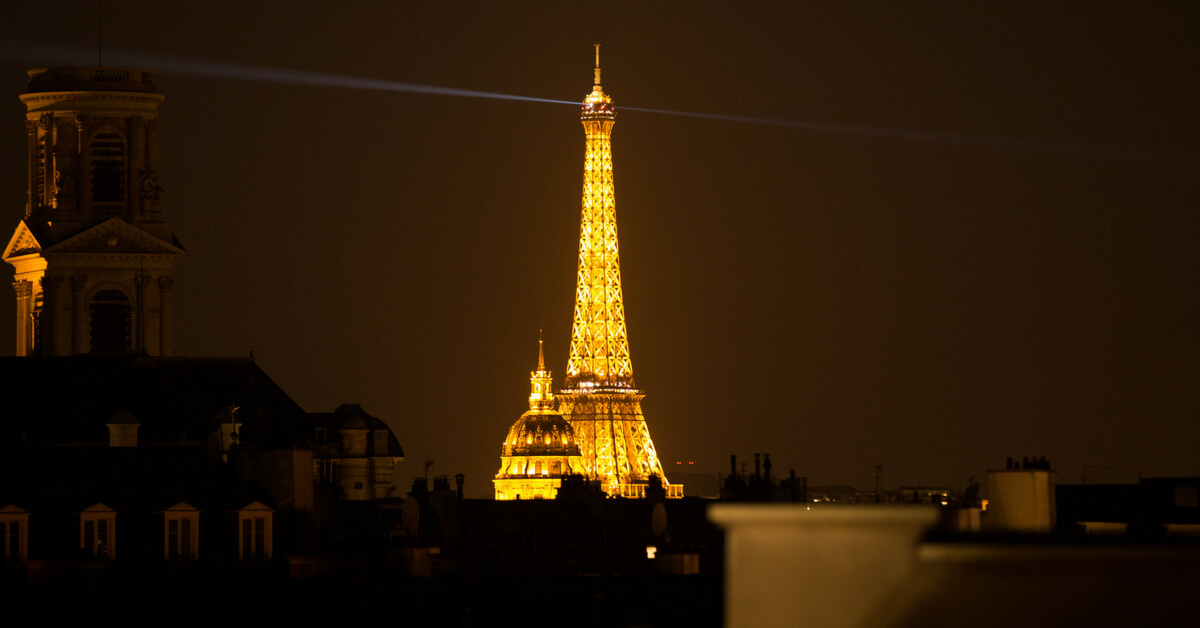 the eiffel tower at night seen from paris rooftops; things to do in paris