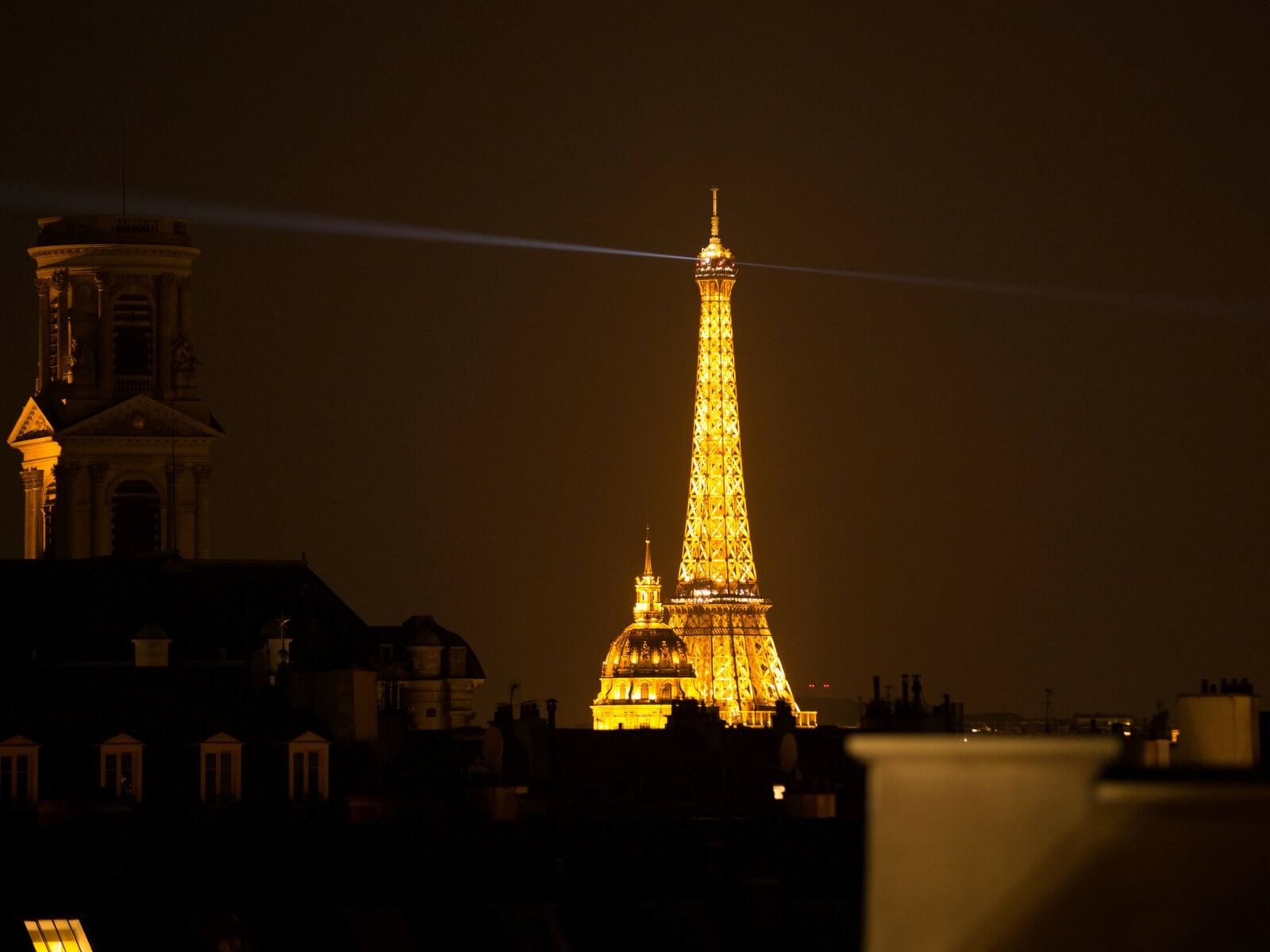 Eiffel Tower at night seen from the Paris rooftops; things to do in paris for first time visitors