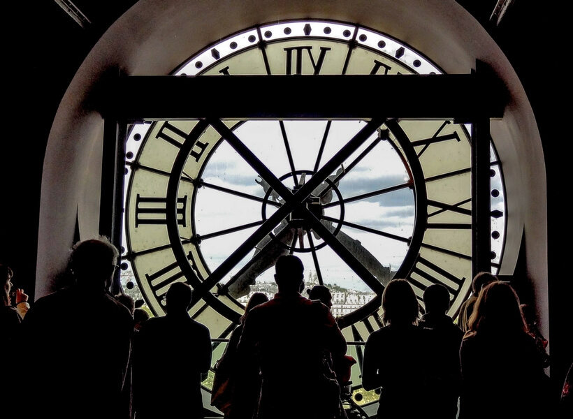 Orsay Clock with people standing in front of it; things to do in paris for first time visitors