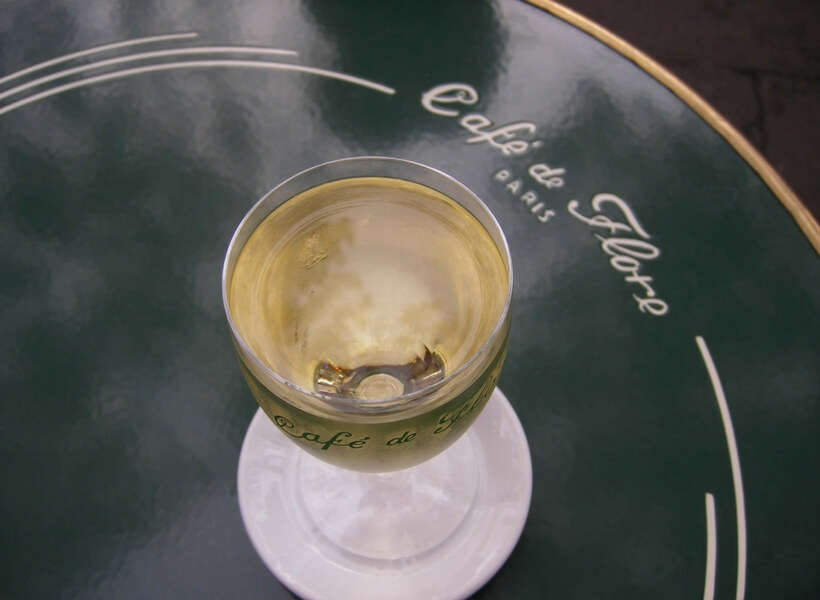 glass of white wine on a café de flore tray; first time in paris