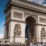 cars driving around the arc de triomphe in Paris