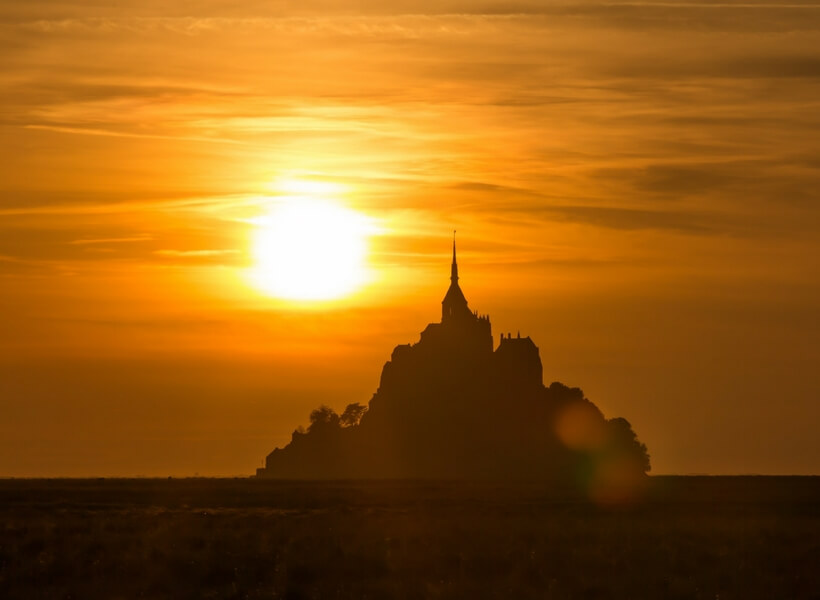 view of the Mont saint michel from a distance; is it possible to visit the mont saint michel as a day trip from paris