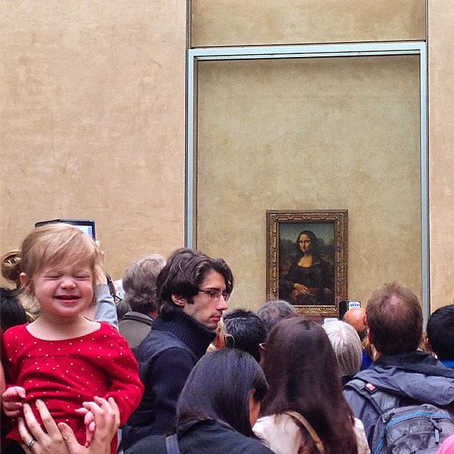 Crowd in front of the Mona Lisa with child making a face; layover in Paris