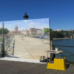 Artitst painting Paris while standing on the pont des arts: visiting paris in august episode