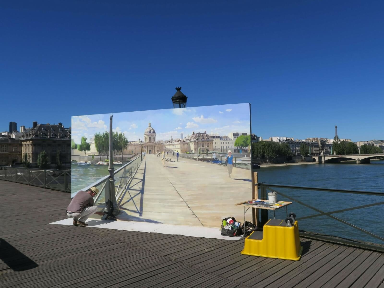 Visiting Paris in August Episode: man painting a Paris landscape on the Pont des Arts on a sunny day in Paris