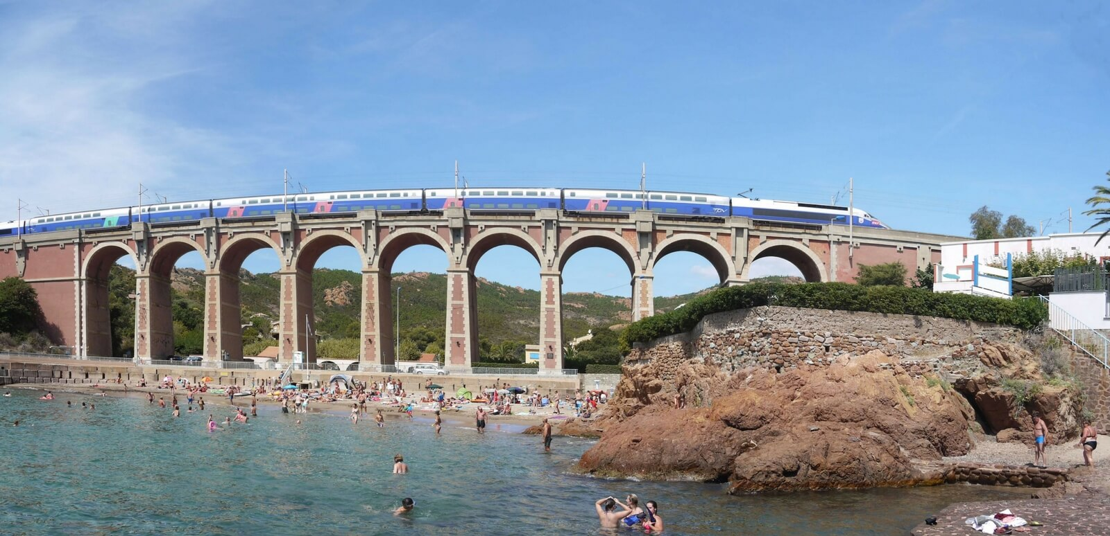 train in france going over a bridge and bathers in a river at the bottom of the bridge
