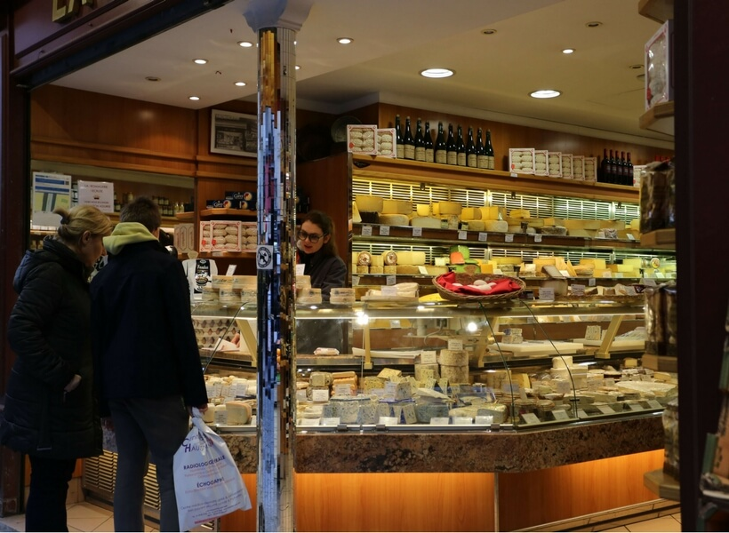 cheese store in paris, two women customers selecting the products they want and a woman clerk helping them