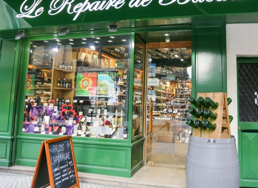 wine store in paris, window display with many wine bottles , promotional sandwich board and wine barrel outside