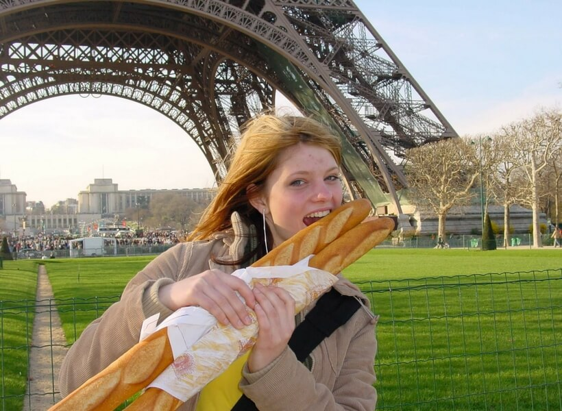 Young woman biting into a French baguette in front of the Eiffel Tower