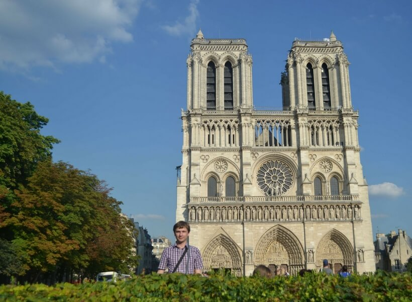 Visiting Paris in August: man posing in front of Notre Dame Cathedral on a summer day