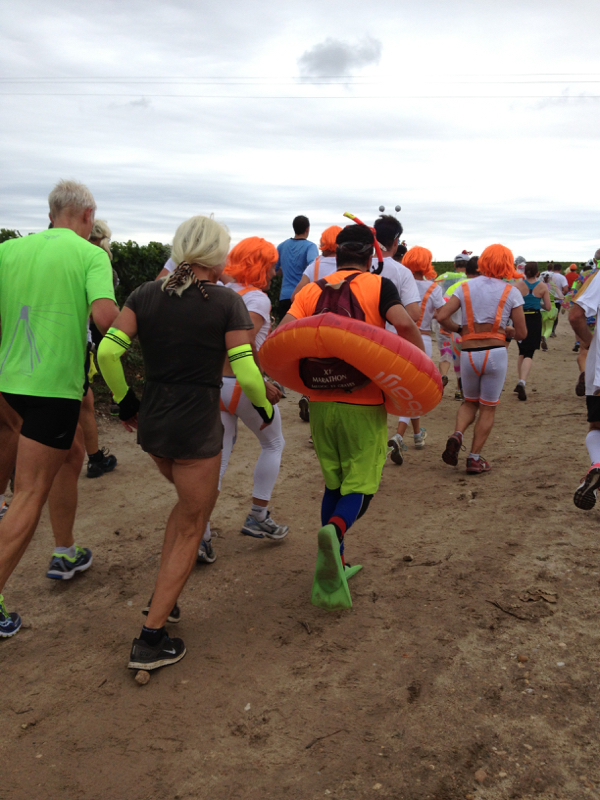 person running the Bordeaux marathon with a swimmer's life preserver and flippers on his feet