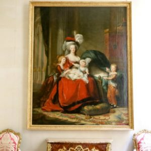 Painting by Élisabeth Louise Vigée-Le Brun. The painting depicts Marie-Antoinette wearing a gorgeous dress and hat, a young girl to her right, a baby on her lap and a young boy pointing to an empty crib on her left