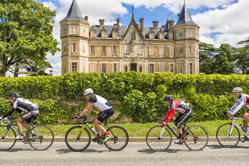 4 cyclists riding past a french chateau