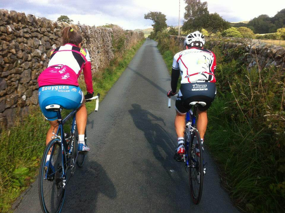 one female and one male cyclists riding on a scenic narrow french road