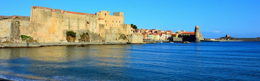 collioure beach, blue water, town in the background