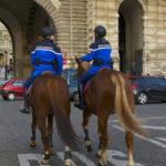 two police officers patroling on horseback in a Paris neighborhood