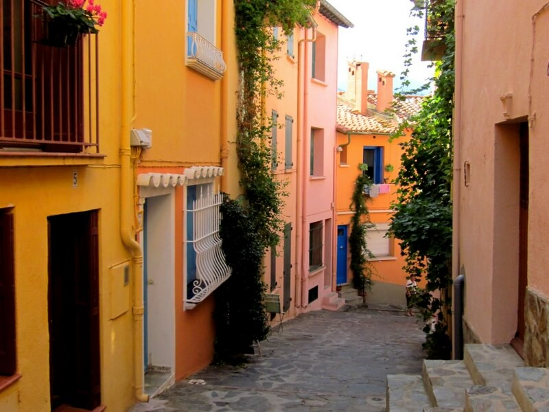 scenic street in collioure, narrow street yellow , orange, and pink buildings