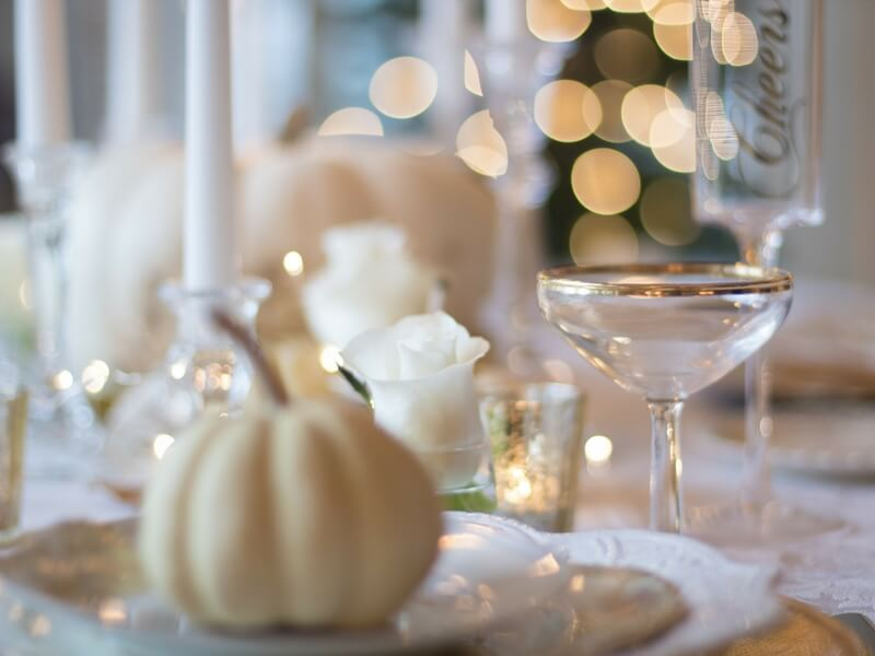 beautiful table decoration with a white squash, candles, and golden reflections