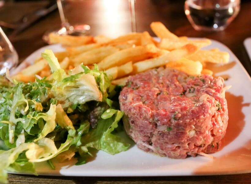 plate of steak tartare, fries and a side salad