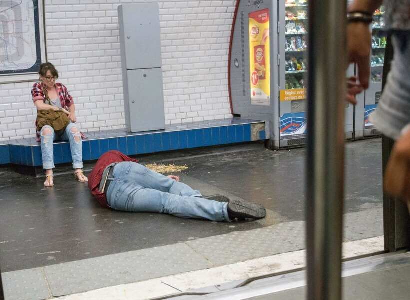 man lying on the metro floor, he has vomited and a woman is making sure he is not chocking
