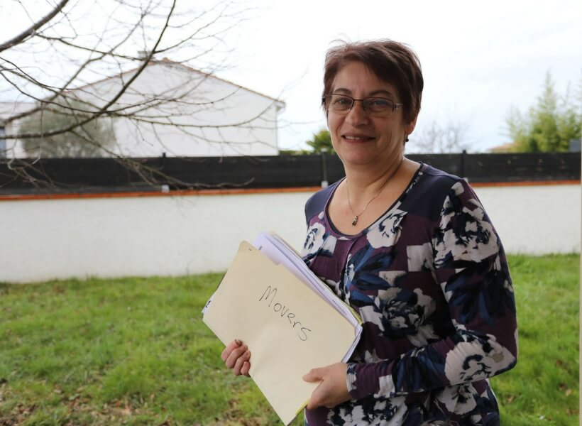 white woman around age 60 holding a folder of paperwork